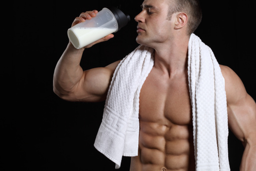 Handsome muscular male with protein shake