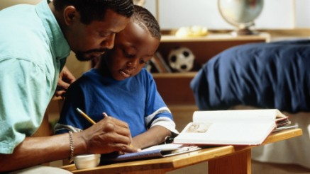 Father helping son (4-6) with homework