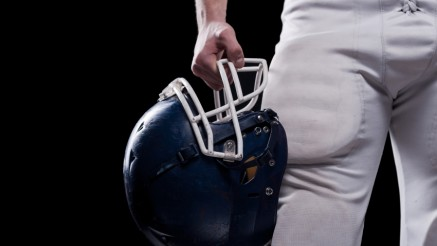 Crash helmet.  Cropped image of American football player holding football helmet while standing against black background